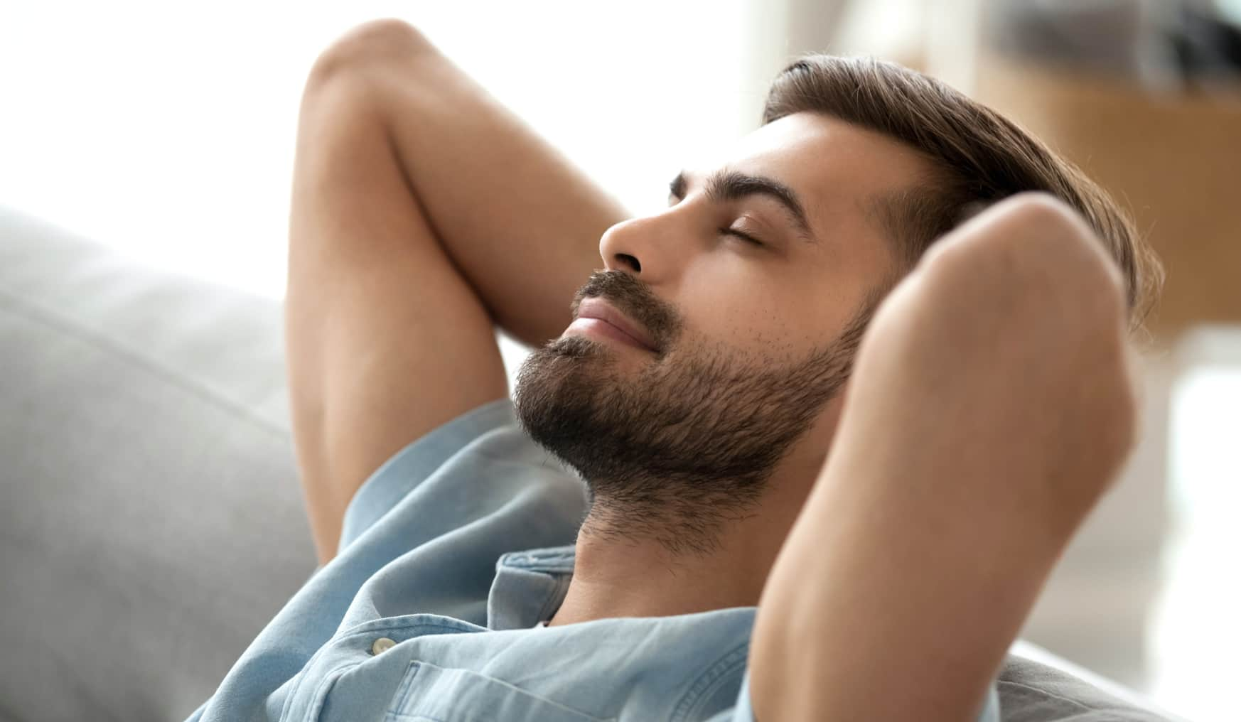 man leaning back on sofa